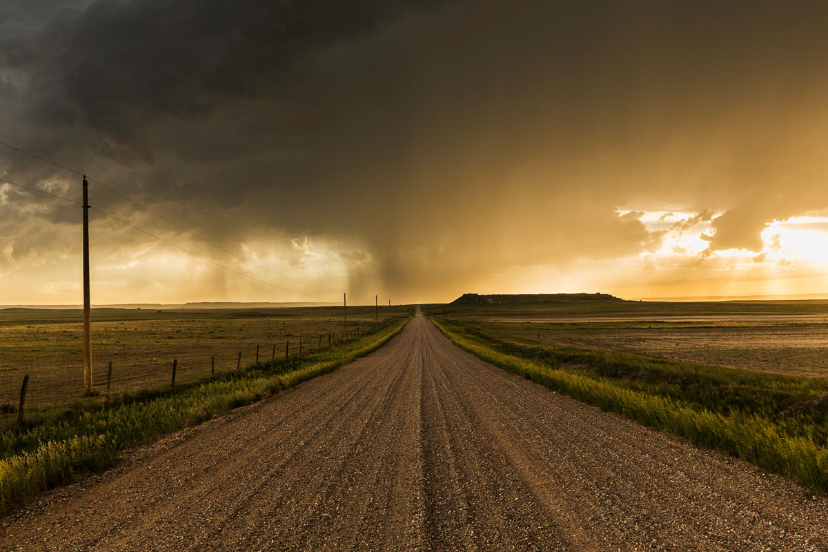Rainstorm Over Gravel Road, Wyoming – Eric Meola