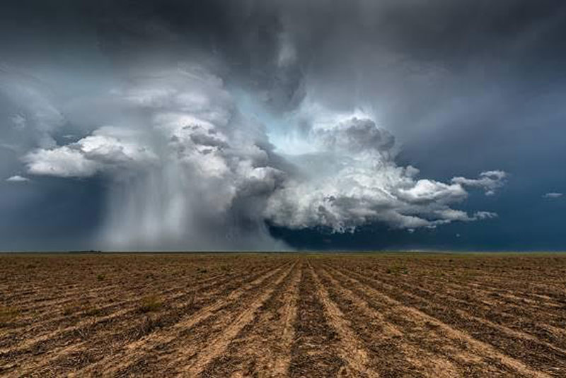 Supercell Hovering Over Plowed Field. Kanorado, Kansas – Eric Meola